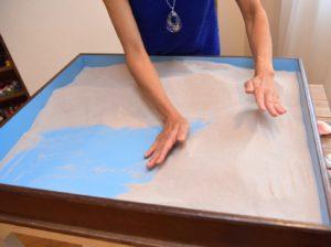 箱庭の砂を触るセラピスト